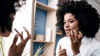 Vrouw kijkt in spiegel naar acne-littekens