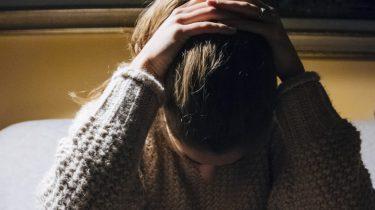 vrouw met handen op hoofd, migraine triggers