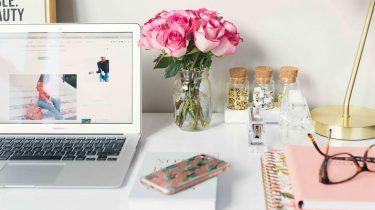 Bureau met laptop, bloemen, notebook en bril, types collega's